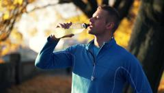 Man drinking isotonic drink after workout, in the autumn park HD Stock Footage