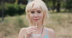 Slow Motion Portrait of happy beautiful caucasian woman drinking juice - stock footage
