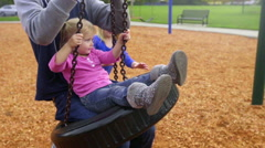 Big sisters pushes dad and little sister on tire swing Stock Footage