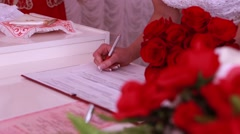 The bride and groom put signatures on wedding ceremony Stock Footage