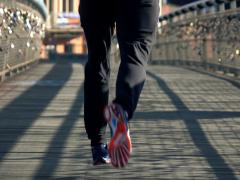 Man jogging across the bridge in city, focus on legs, shot at 120fps NTSC Stock Footage