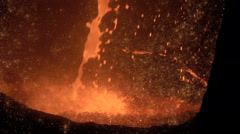 Molten iron is poured into a vat slow motion closeup Stock Footage