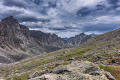 Gloomy skies over the slopes of the mountain tundra, in July. - stock photo