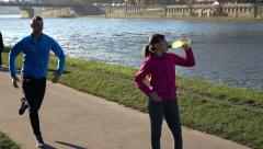 Woman drinking water after workout, man jogging in the city street, 240fps HD Stock Footage