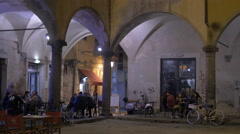 Tourists relaxing under a building with arches and columns in Pisa Stock Footage