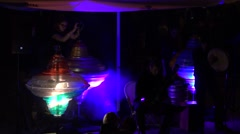 Exciting show girls spin giant light whirligig tools with smoke rising. 4K Stock Footage