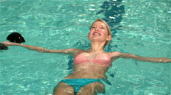 Fit woman relaxing in the pool Stock Footage