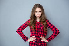 Angry young woman standing with arms akimbo - stock photo
