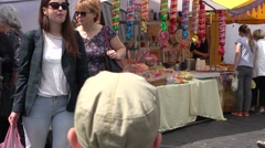 Colorful sweets sold in city street fair and people with children. 4K Stock Footage