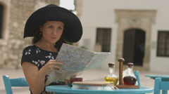 Pretty female tourist sitting in cafe with map in hands, examining journey route Stock Footage