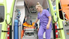 Emergency medical service paramedic taking stretcher out of an ambulance Stock Footage