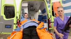 Emergency medical ambulance service paramedics fixing patient on stretcher Stock Footage