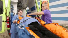 Emergency medical service paramedics female patient on ambulance stretcher Stock Footage
