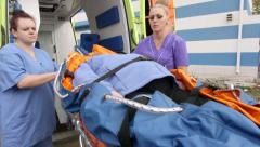 Emergency medical ambulance service paramedics crew fixing  patient on stretcher Stock Footage