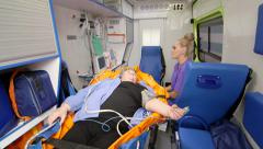 Provide basic emergency medical care and transportation for patient in ambulance Stock Footage