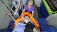 Paramedic holding patient head wearing oxygen mask in ambulance Stock Footage