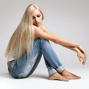 Blonde woman in ragged jeans and vest - stock photo