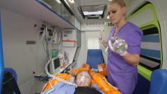Paramedic provide emergency medical care to patient in ambulance preparing drip Stock Footage