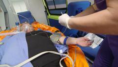EMT provide emergency medical care to patient in ambulance intravenous infusion Arkistovideo