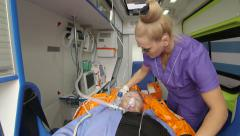 Emergency medical technician provide critical care to patient in ambulance Stock Footage
