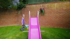 4K Little girl playing on a slide in the back garden at home - stock footage