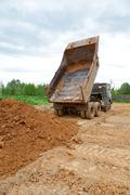 dump-body truck unloads a ground on the land - stock photo