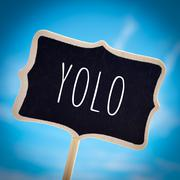 signboard with the word yolo, vignetted - stock photo