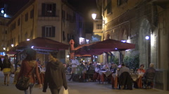 Tourists walking and relaxing at a restaurant on Via Santa Maria, Pisa Stock Footage