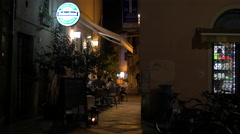 Tourists relaxing at an outdoor restaurant located on a narrow street in Pisa Stock Footage