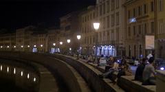 Tourists relaxing on the riverside on Lungarno Antonio Pacinotti, Pisa Stock Footage