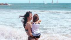 Mother and daughter hug kissing on the sea beach - stock footage