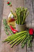 Still life with olive oil asparagus, avocado, pepper and rosemary - stock photo