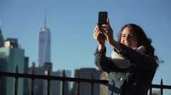 A beautiful woman taking selfies, NYC skyline in background Stock Footage