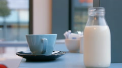 Milk jug and cup on cafe table - stock footage