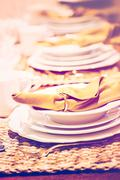 Table set with plates and silverware for Holiday dinner - stock photo