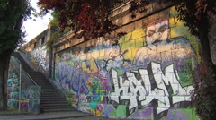 Grafitti on wall in Vienna with shadows of passing pedestrians - stock footage