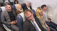 Passenger on flight woken up as the person behind pulls on his seat to stand up Stock Footage
