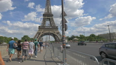 People driving cars and walking on Jena Bridge, next to Eiffel Tower, Paris Stock Footage