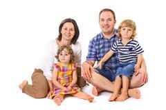 Happy family of four smiling - stock photo