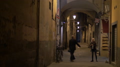 Tourists walking at night on a street in Pisa Stock Footage