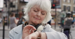 Slow Motion Portrait of happy mature old woman using smart watch Stock Footage
