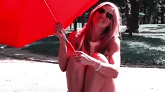 Young Pretty Blonde Caucasian woman sitting in Park with Red Umbrella Stock Footage