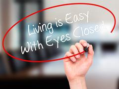 Man Hand writing Living is Easy With Eyes Closed with black marker Stock Photos