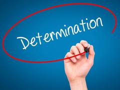 Man Hand writing Determination with black marker on visual screen. - stock photo