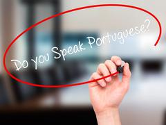 Man Hand writing Do you Speak Portuguese? with black marker on visual screen Stock Photos
