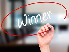 Man Hand writing Winner with black marker on visual screen. - stock photo