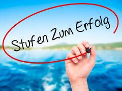 Hand writing Stufen Zum Erfolg (Steps to Success in German) with marker - stock photo