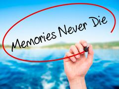 Man Hand writing Memories Never Die with black marker on visual screen Stock Photos
