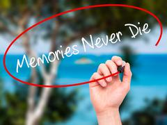 Man Hand writing Memories Never Die with black marker on visual screen - stock photo