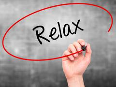 Stock Photo of Man Hand writing Relax with black marker on visual screen.
